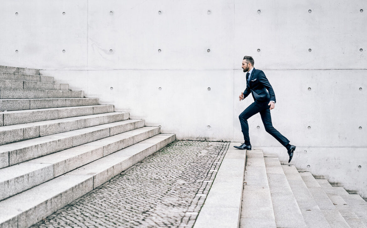 Young businessman running up stairs
